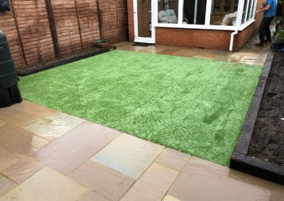 Raj sandstone patio with wet look Finish, reclaimed sleeper flower beds and artificial grass