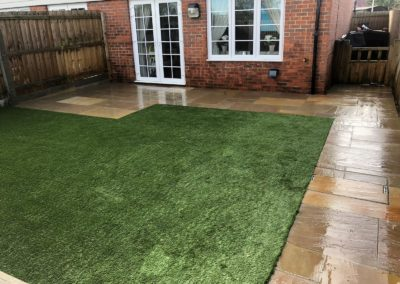 Raj sandstone patio and path, with artificial grass and concrete shed base in Clandon