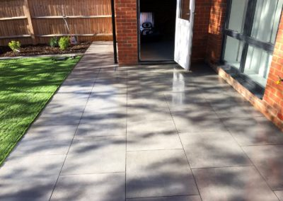 Grey porcelain tiles with artificial grass and planting areas